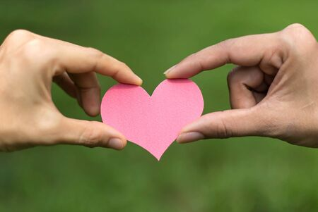 Two hands holding pink heart paper against nature background Stock Photo