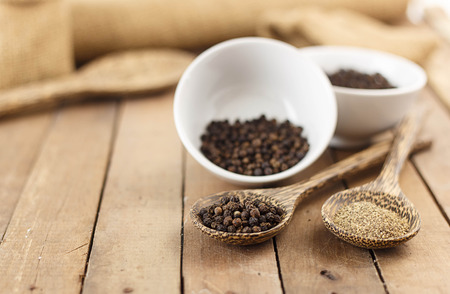 Spicy herbs - dry black pepper and ground pepper on wooden spoon Banque d'images
