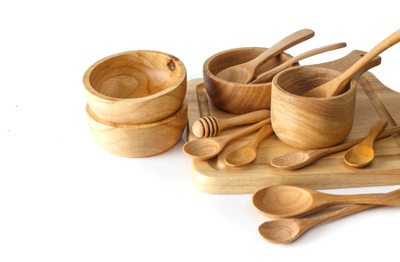 Group of wooden utensils on white background with space on left
