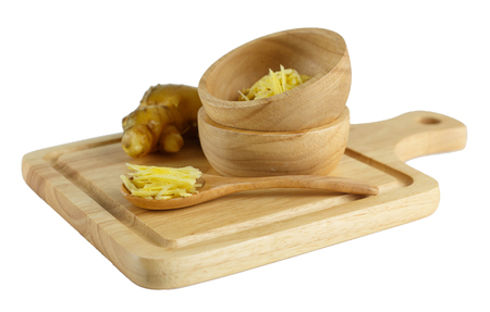 Sliced ginger on wooden spoon - fresh and spicy on white