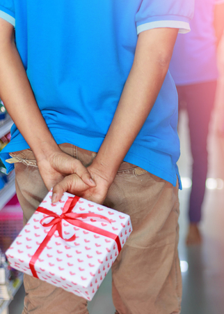 Man holding giftbox behide his back for surprise