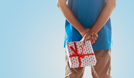 Surprise present - man standing and hide giftbox against soft background