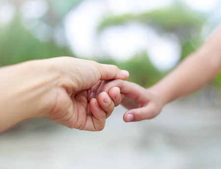 Mother holding child hands with love and care against nature background