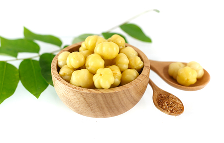 Bowl of preseved star gooseberry and leaves on white background