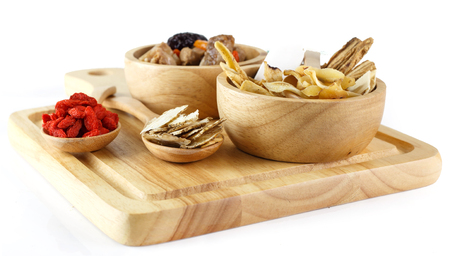 Chinese herbals on wooden spoon and bowl of soup on white Banque d'images