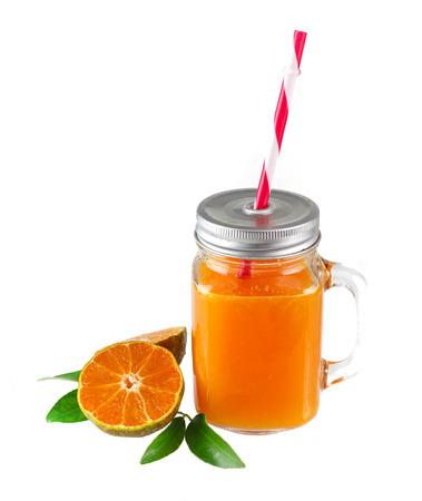 Glass of fresh orange juice and slice orange with leaves  on white