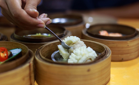 Chinese foods for breakfast - hand with fork take fresh and delicious dim sum