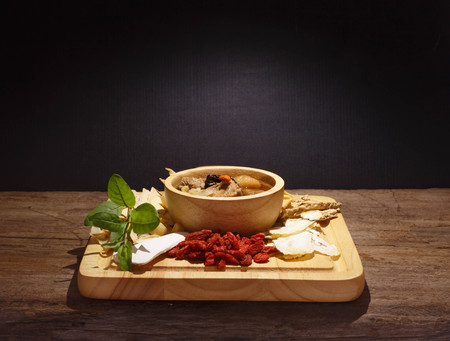 Bowl of chinese soup and herbal medicines on wood against black
