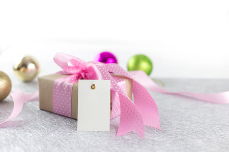 Beautiful giftbox with pink ribbon and blank tag for happy celebration