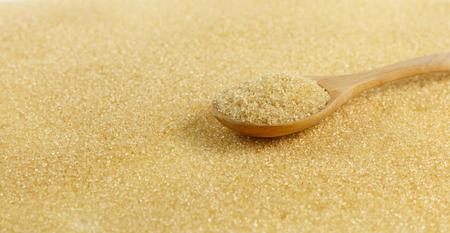 Spoon of brown sugar put on heap of sugar