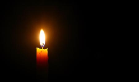 Lumière de bougie jaune brûler sur fond noir