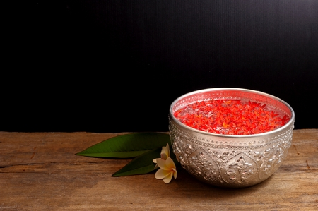 Bowl of water and flowers for songkran festival on wood against black background 스톡 콘텐츠