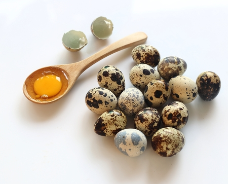 Group of raw quail eggs and wooden spoon on white background