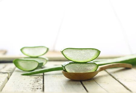 Close up liced aloe vera on spoon herbal medicine for skin and hair on white