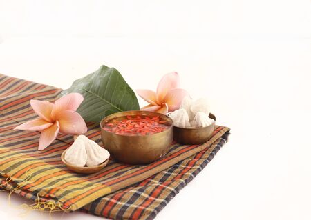 Thai Songkran accessories - bowl of water,flower and clay  on thai fabric  isolated on white