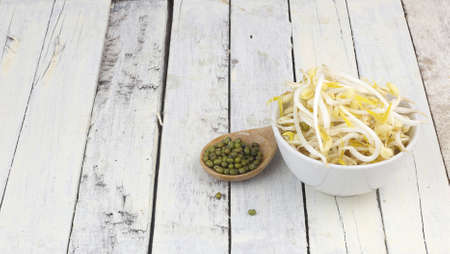 Bowl of raw mung bean sprouts and spoon of mung beans on white wooden table Stock Photo