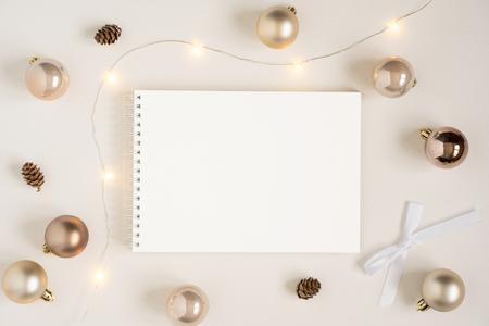 Elegant blank paper stationery photo based mockup. Horizontal landscape festive presentation for art design. Minimalist stylish text template. Flat lay of notepad, Christmas lights, gold garland