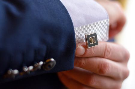 cuff: a man fastens a cuff-link on a cuff
