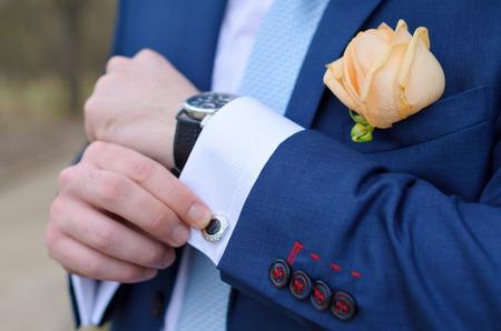 cufflink: masculine hands hold a cuff-link suit Stock Photo