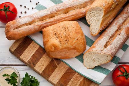 ciabatta: Sliced bread Ciabatta and rosemary on wooden background Stock Photo