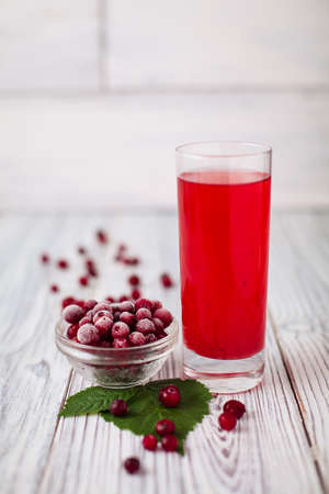 cranberry juice: Cranberry juice glass red, hoarfrost wooden leaves Stock Photo