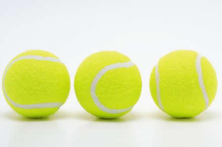 three yellow tennis balls on white surface