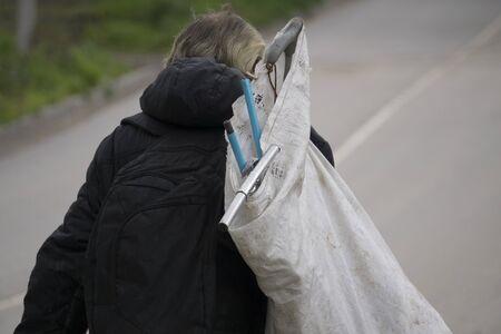 a homeless man walks with a bag