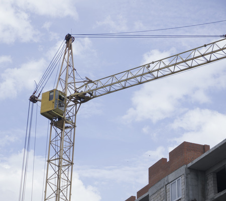 residential construction: Construction site. Construction cranes and high-rise building under construction against blue sky.