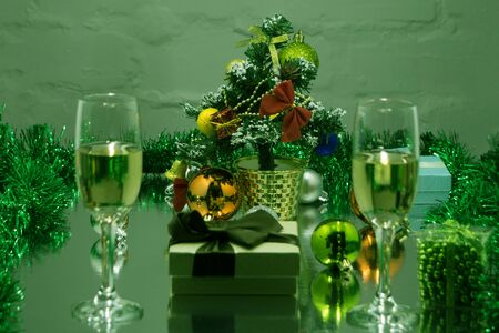Champagne flutes with golden bubbles on dark green light bokeh background with space for text