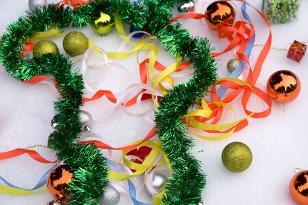 Christmas gifts and balls scattered on a table with an old clock