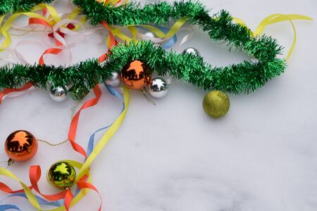 Christmas decorations are scattered on the table. Balls and garland of blue, golden and red colors on the table