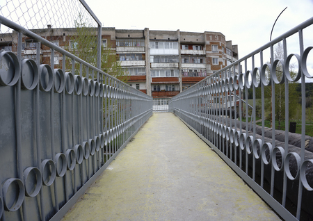 End of pedestrian bridge over suburban road and curved continuation of wooded recreational trail