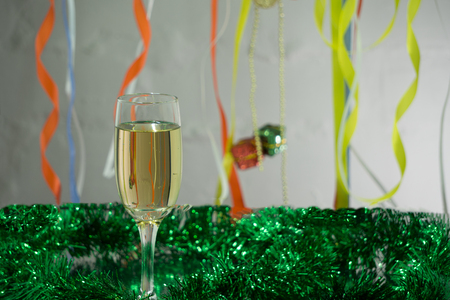 Christmas and New Year greeting card template made of golden and green tinsel with red christmas balls, red ribbon, orange candle and two glasses of champagne with copy space, horizontal view