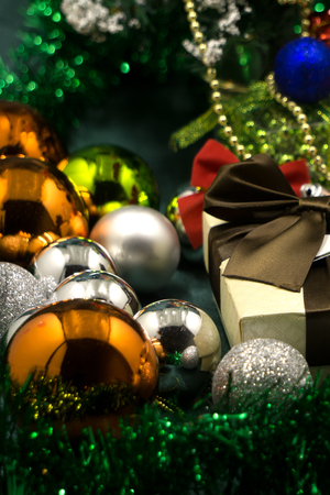 Christmas balls and Christmas gift on grey wooden background Stock Photo