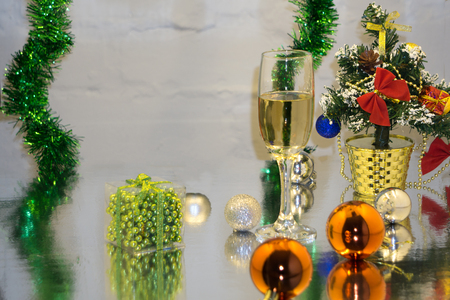 Greeting card made of christmas and yew year decoration balls, tinsel, candle and two glasses of champagne with reflection. Stock Photo