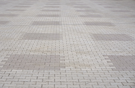 Texture of gray and yellow patterned paving tiles on the ground of street, perspective view. Cement brick squared stone floor background. Concrete paving slab flagstone. Sidewalk pavement pattern.