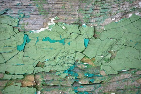 Flaky green paint on the wall. Wall with old peeling and cracked paint.