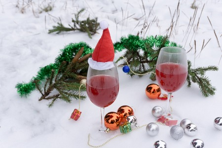 Wine glass with red sparkling wine on a table on a blurred background of christmas lights Stock Photo