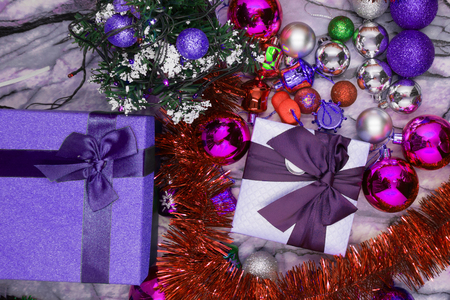 Gifts under a decorated Christmas tree. A green striped gift box with a purple-orange metallic bow. A wooden drawer filled with ornaments under a Christmas-tree with red balls.