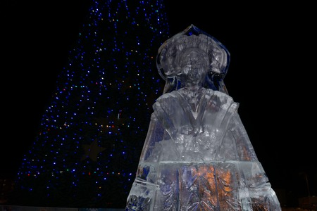 Figure of the snow Maiden and cut out of ice near the Christmas tree .