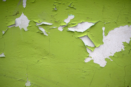 Old flaky white paint peeling off a grungy cracked wall