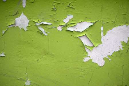 Oude schilferige witte verf peeling van een grungy gebarsten muur