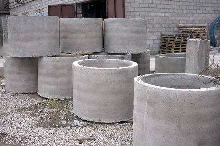 Concrete ring wells with different diameters and gray lie in the street