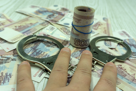 Money and handcuffs are lying on a table