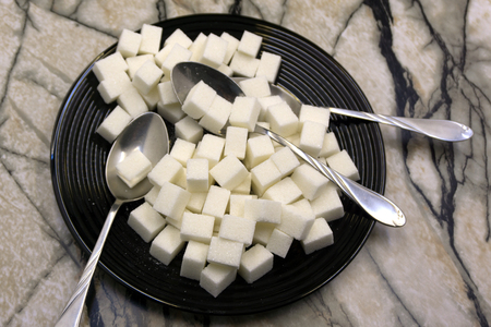 Too much sugar. Cubes of sugar in the plate. Concept of unhealthy eating