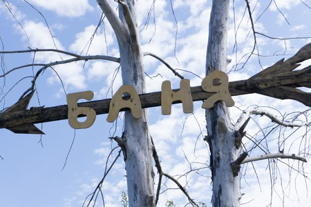 Metal artwork spelling out the word bath on a knotty pine wall