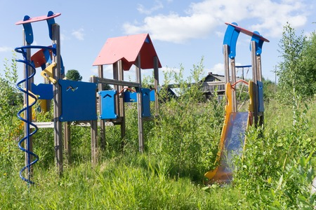 Old neglected playground equipment, overgrown with weeds Reklamní fotografie