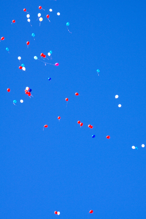 Holiday. Multi-coloured balloons depart to the sky