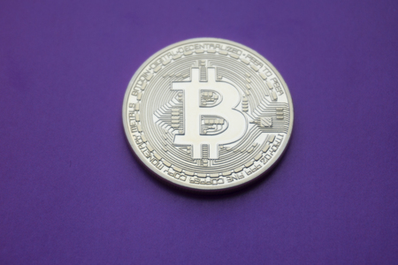 Golden Bitcoins (digital virtual money) on a purple background. Фото со стока