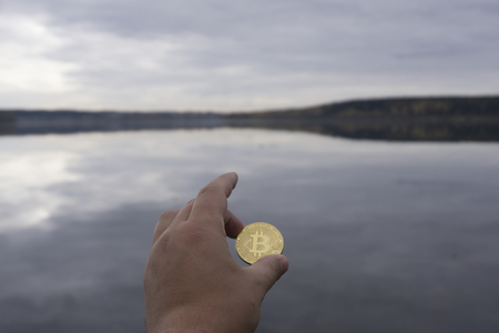 Bitcoins are in hand on the background of water Stock Photo